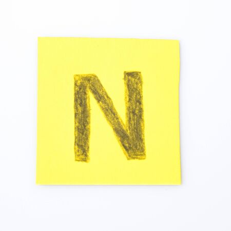 N alphabet letter handwrite on a yellow paper composition