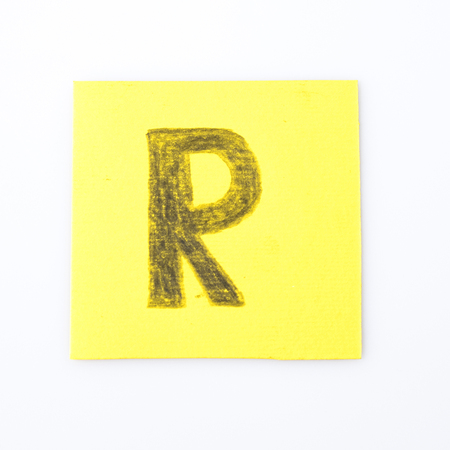R alphabet letter handwrite on a yellow paper composition