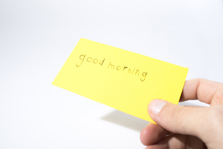 Good morning handwrite with a hand on a yellow paper composition