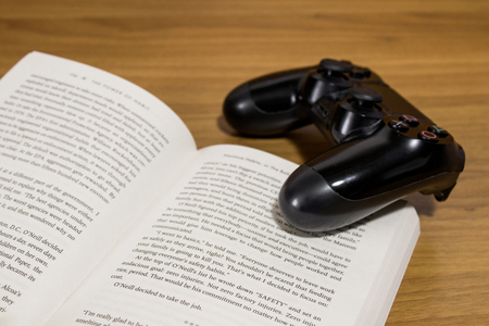 Study distraction, reading or playing videogames with a book and a gamepad composition Stock Photo