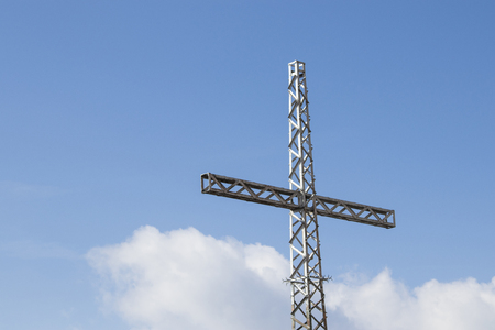 Mountain cross in a beautiful blue sky and clouds composition