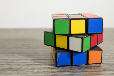 Colored rubik cube on a decrated wood table composition