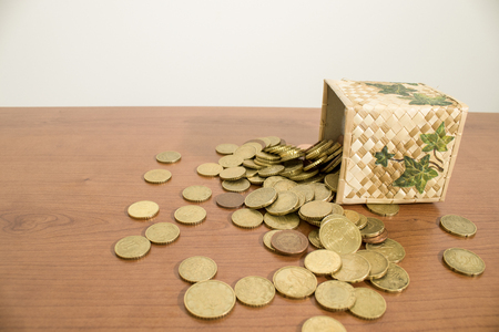 Box full of euro coins on a wood table composition
