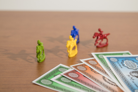 Colored fake banknotes and fake horses on a wood table composition