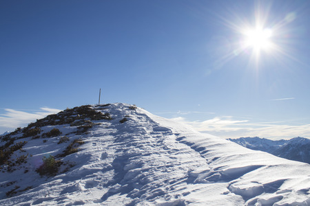 Mountain top with a shining sun during winter composition