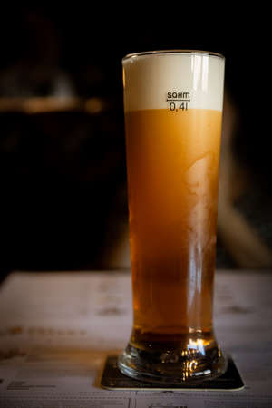 ruby-colored beer with dense foam in the glass Imagens