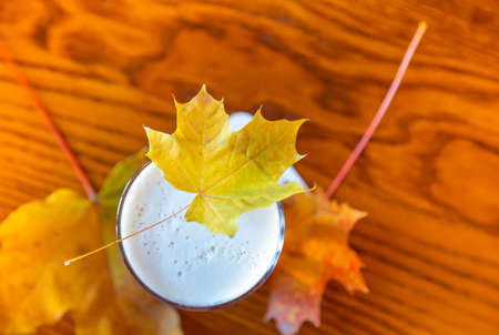 maple leaf lies on top of a glass of beer
