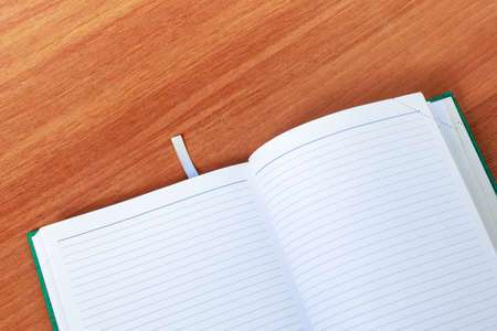 Empty open Notepad for writing lies on a wooden table, top view, minimalism. 免版税图像