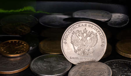 coin ruble between other rubles and green mirror background