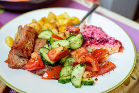 a plate with fried tuna, potatoes and fresh salad on the table