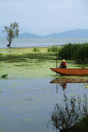 Chinese fisherman in an orange boat on a lake near Dali Stock Photo