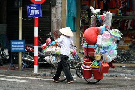 Hanoi, Vietnam, August 18, 2008 - Vietnamese woman with bicycle