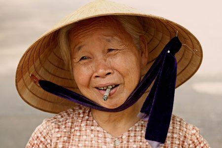 Hoi An, Vietnam, August 21, 2008 - Cigarette Woman in Vietnam Editorial