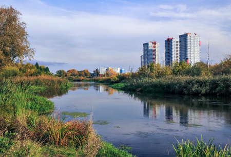 urban housing: building, autumn, environment, urban, house, landscape, river, apartment, area, picturesque, city, housing, multystoried,  reflection,  russia, region,  water, panorama, day,golden, view, tree, yellow, air, weather, scenery, cloudy,modern architecture Stock Photo