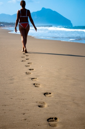 Human footprints on the sand to the sea photo