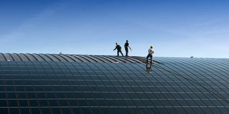solar thermal: Installation of solar panels on the roof of a building Stock Photo