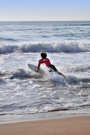 Man dives into the sea waves with surfboard Stock Photo - 13047316