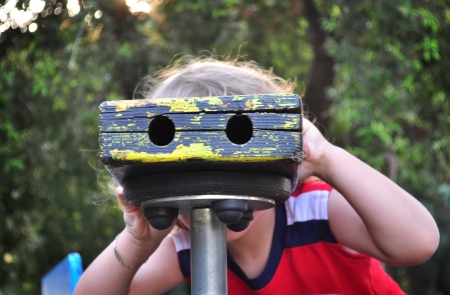 Curious child looking through toy binoculars photo
