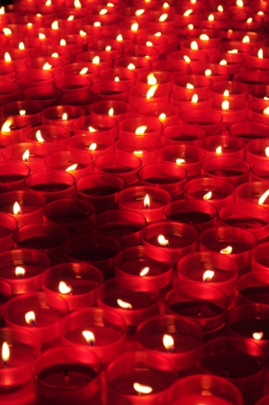 Many red votive candles light the darkness in church photo