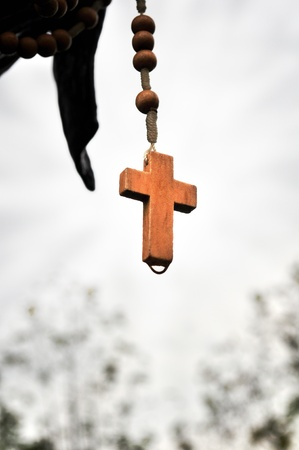 Cross of a wooden rosary on white background photo