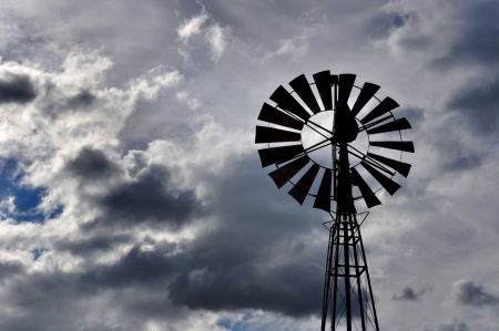 leaden: Wind pump for well water with a leaden dark cloudy sky Stock Photo