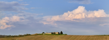 Panoramic view of a farmhouse in the countryside surrounded by vineyards cloudy sky photo