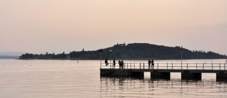 Pier on the lake at sunset with island in the background photo