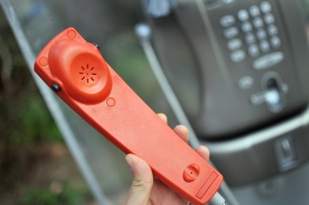 Hand holding a red handset of a public telephone photo