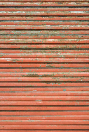 security shutters: Old and rusty red store front Closed Roller shutter