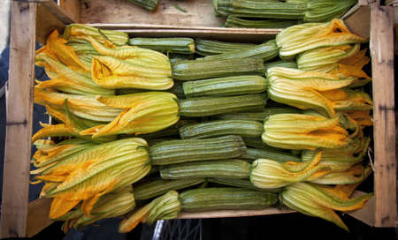 bushel: A create full of flowering zucchini in a market
