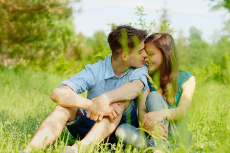 romantic young couple sitting in a field  photo