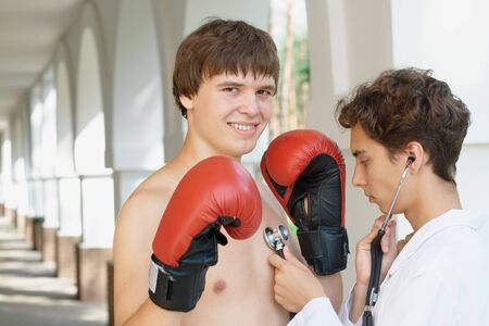 Photo of a docotr cheking a boxer (with copy space) photo