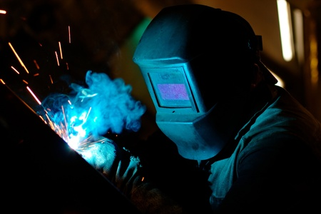 Photo of a welding process wtih sparks flying around (with copy space)