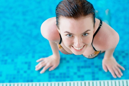 Smiling young girl at the swimming pool photo