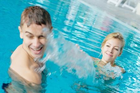 Teenage couple splashing in a swimming pool photo