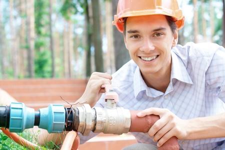 tuberias de agua: Sonriente joven trabajador reparar una tuber�a al aire libre