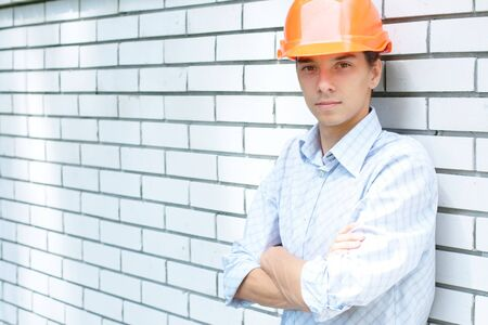 Young worker standing near a white wall (with copy space) photo