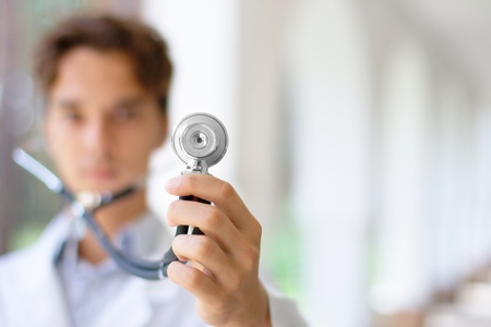 listening to heartbeat: Doctor holding a stethoscope Stock Photo