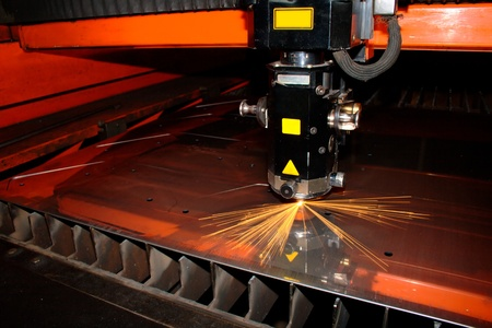 laser cutting: Industrial laser with sparks flyiing around (with copy space)