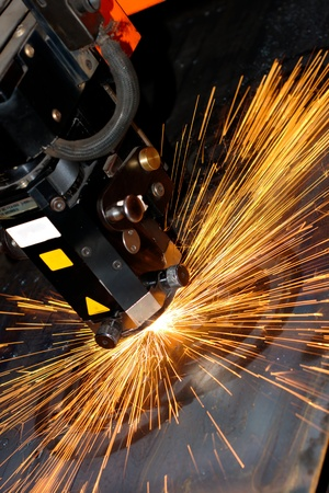 metal cutting: Industrial laser with sparks flyiing around (with copy space)