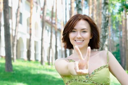 Young girl with two fingers up with a building at the background photo