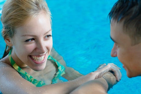 Young girl flirting with a boy at the swimming pool photo