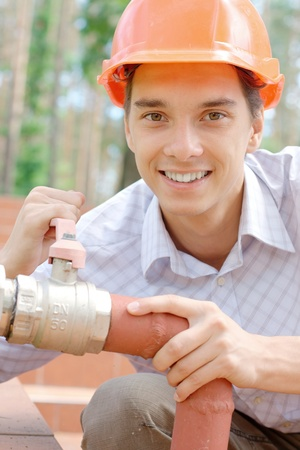 Smiling young worker repairing a pipe outdoors photo