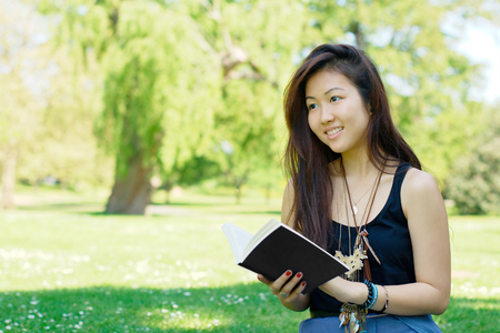 allergy questions: Smiling asian girl reading a book at the park Stock Photo