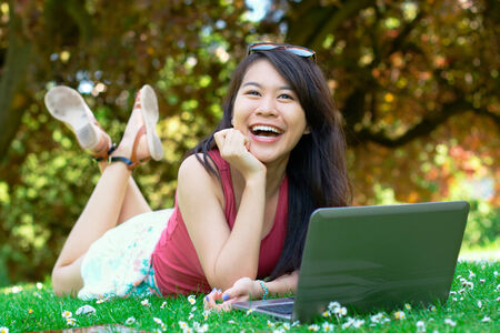 allergy questions: Smiling asian girl with a laptop at the park
