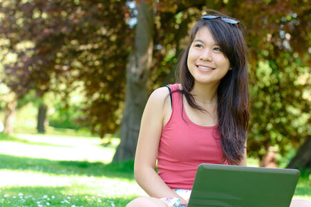 Smiling asian girl with a laptop at the park