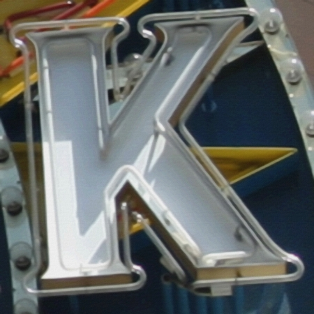 Painting of the letter K in neon with canvas texture. 免版税图像