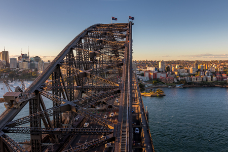 The sun is setting on the Sydney Harbour Bridge with the afternoon traffic. Stock Photo