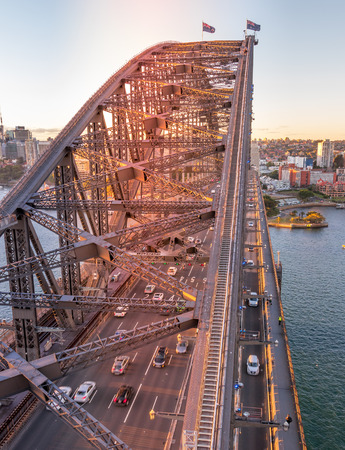 The sun is setting on the Sydney Harbour Bridge with the afternoon traffic. Stok Fotoğraf