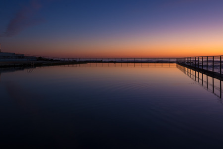 Dawn sky reflection in a seaside coastal pool. Early morning, twilight colours. 免版税图像